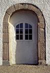 Den medeltida sydportalen i släpljus, där relieferna syns tydligt.
